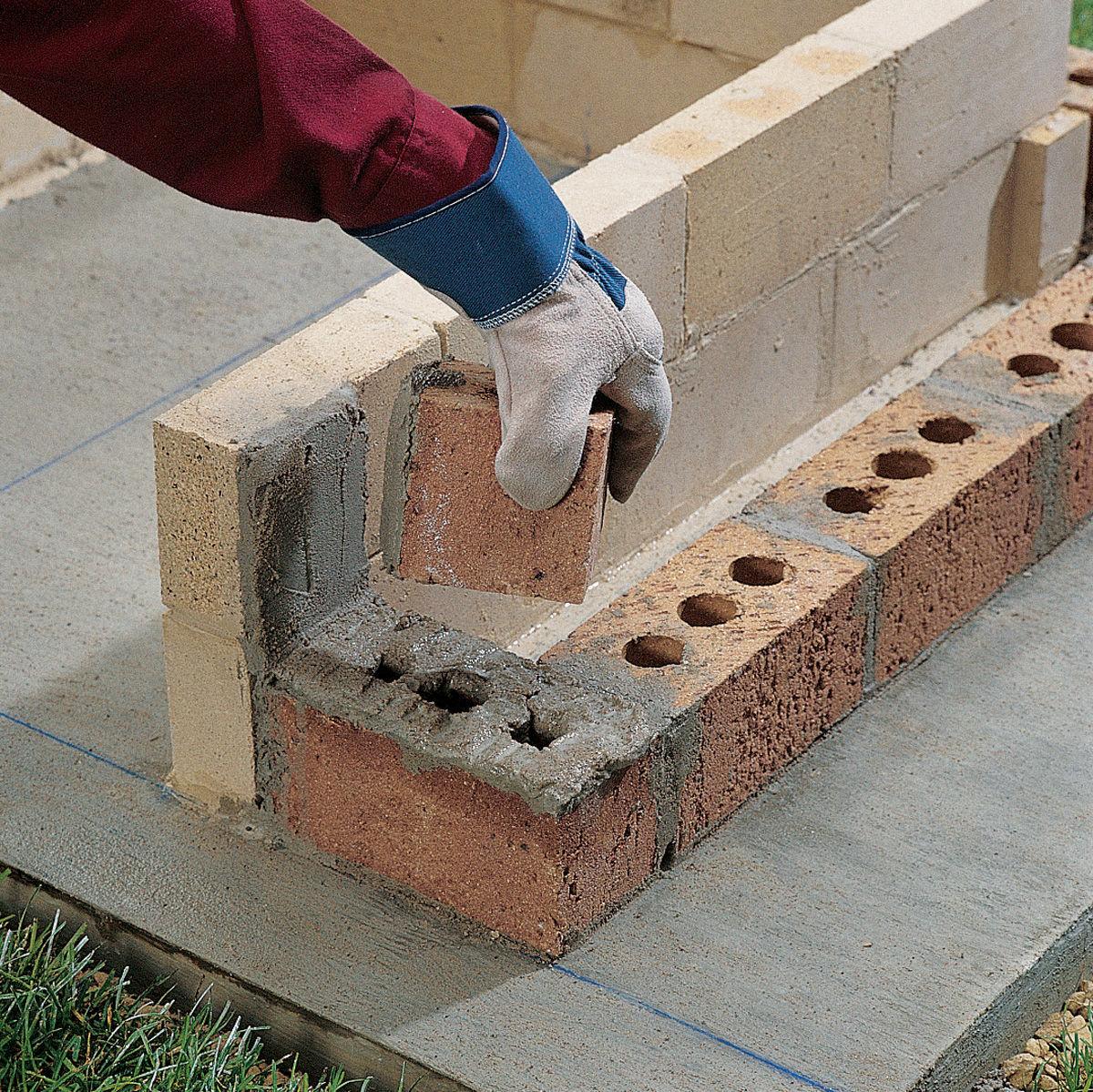 Первые ряды наружных стен мангал-гриль из кирпича